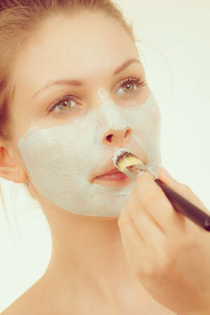 Young woman applying with brush green white mud mask to her face. Teen girl taking care of oily skin, purifying the pores. Beauty treatment. Skincare.