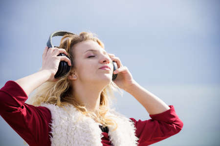 Relaxed woman listening to music while being outdoor. Teenage female wearing headphones having great time chilling outside. Standard-Bild