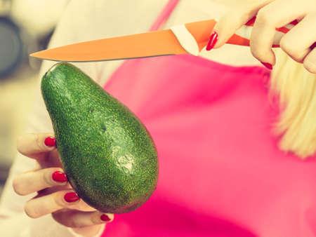 Woman cutting, preparing green vegetable, delicious avocado using kitchen knife. Female wearing apron making food.