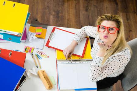 Happy business woman feeling energetic sitting working at desk full off documents in binders showing kiss blowing Standard-Bild