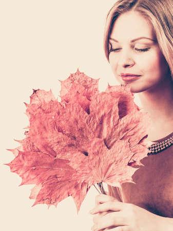 Autumnal natural decorations concept. Woman holding autumn leaf. Studio shot on white background. Reklamní fotografie