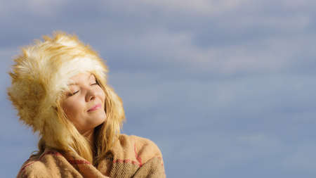 Teenage female spending time outdoor on the beach during autumn weather. Wearing sweater, scarf and fur hat.
