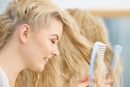 Pretty young woman taking care of haircare, brushing wet blonde hair after taking a shower feeling fresh.