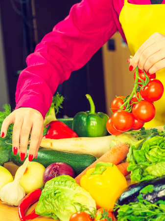 Woman picking tomatoes from healthy colorful vegetables on kitchen table. Dieting, vegetarian local fresh food, natural source of vitamins.