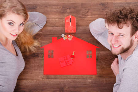 Housing finances real estate family future concept. Couple on floor with symbols. Man with lady next to home piggy bank models. 版權商用圖片 - 128769516