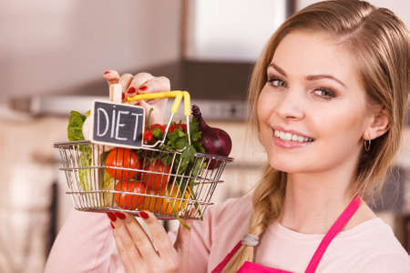 Chef happy woman holding shopping basket with diet sign and many colorful vegetables. Healthy eating lifestyle, vegetarian food.
