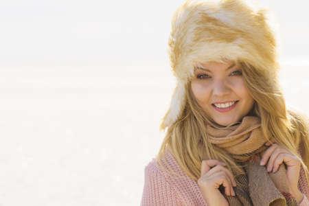 Pretty fashion model wearing furry warm hat enjoying sun during spring or autumn weather.
