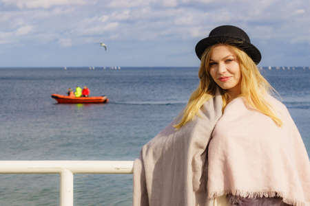 Happy positive teen girl in hat enjoying sunny day outdoors on sea coast