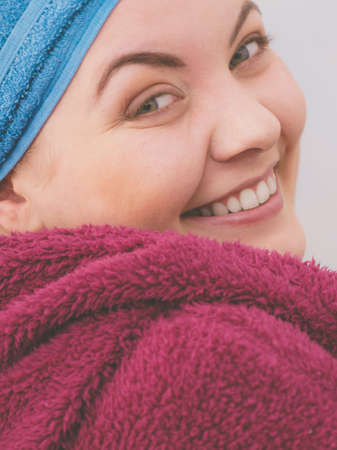 Young woman in bathroom after taking shower feeling clean and relaxed wearing towel and bathrobe