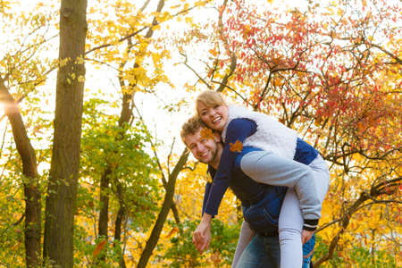 Love healthy relationship and dating concept. Lovers couple having fun, man giving piggyback to woman in autumn park. Young adults girlfriend and boyfriend hugging happy.