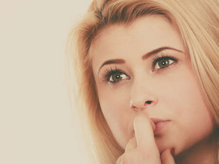 Closeup portrait of thinking blonde woman making serious neutral face, contemplating about things and ideas. Stock Photo