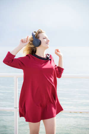 Relaxed woman listening to music while being outdoor. Teenage female wearing headphones having great time chilling outside. Фото со стока