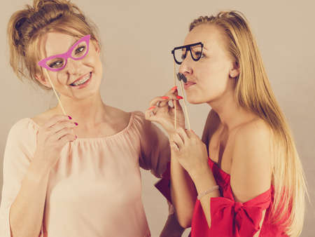 Happy two women holding paper decoration photo booth mask glasses and moustache on stick, having fun. Wedding, birthday and carnival funny accessories concept.