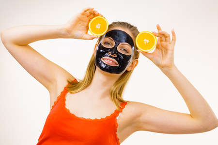 Woman with carbo detox black peel-off mask on face holding orange fruit. Teen girl taking care of oily skin, cleaning the pores. Beauty treatment. Skincare. 写真素材