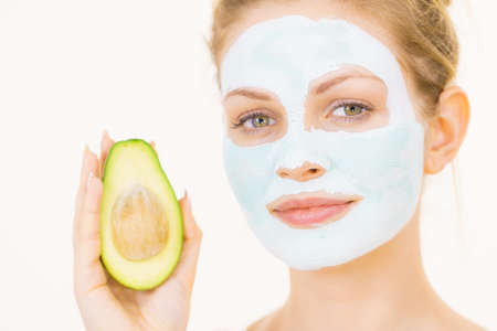 Young woman with white green mud mask on face holding avocado fruit. Teen girl taking care of her skin, cleaning the pores. Beauty treatment. 写真素材