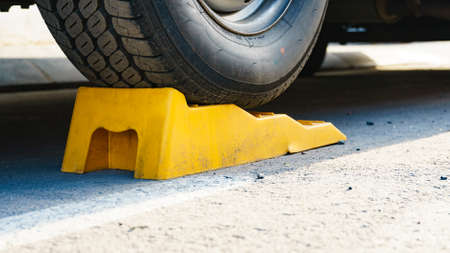 Camper leveling yellow block in use. Leveler ramp chock blocks for rv travel trailer. Accessories for motorhome. Stock Photo