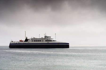 Ferry boat on water fjord, cloudy rainy weather, Lofoten Norway. Travel and tourism. Фото со стока