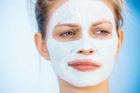 Young woman with white dry mud mask on face, against blue. Teen girl taking care of oily skin, cleaning the pores. Beauty treatment. Skincare. 写真素材