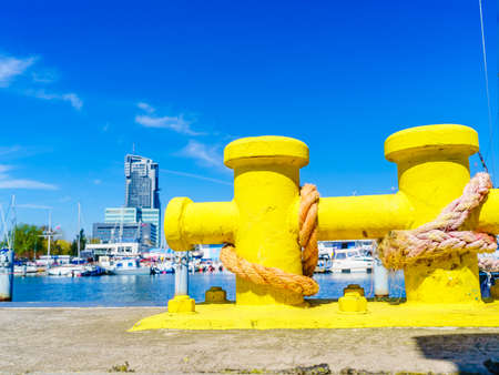 Shipping objects concept. Sailing ropes tied around yellow marina bollard. Outdoor shot on sunny day.