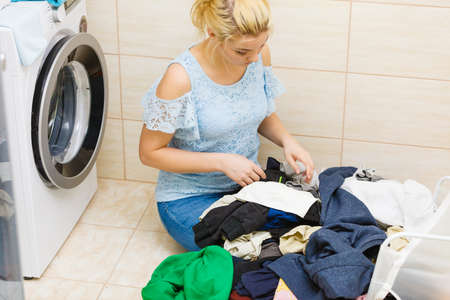 Woman in bathroom sorting clothes laundry for washing in machine. Household duties. 写真素材