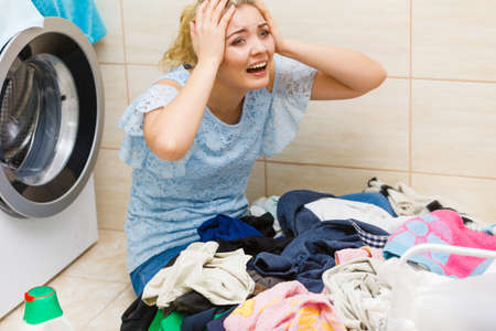 Unhappy woman in bathroom with pile of dirty clothes laundry and damaged washing machine. Hard work, household duty.