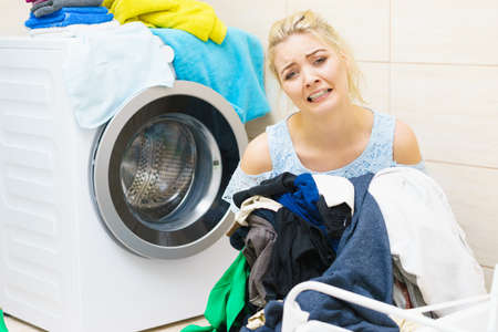 Sad woman having a lot of laundry to make. Unhappy female surrounded by big clothing piles stack sitting next to washing machine being tired houseworking.