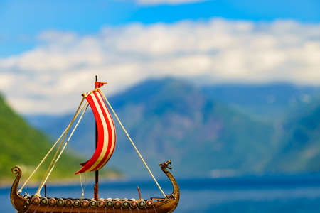 Old wooden viking longboat sails, drakkar boat on fjord shore in Norway. Tourism and traveling concept