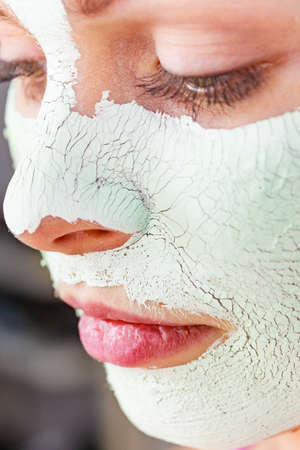 Close up woman with green white mud mask on face. Teen girl have dry cracked cosmetic on skin. Beauty treatment. Skincare. Stockfoto