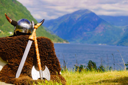 Viking helmet with weapons on fjord shore in Norway. Tourism and traveling concept Stok Fotoğraf