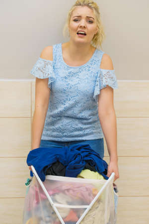 Woman having troubles with holding big laundry basket full of colorful dirty clothes. Bathroom utensils concept. Standard-Bild - 129683160