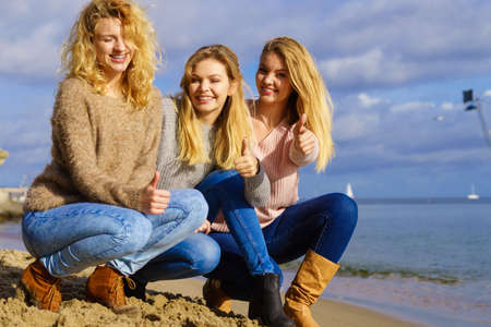 Three fashionable women wearing sweaters during warm autumnal weather spending their free time on sunny beach. Fashion models outdoor 스톡 콘텐츠 - 130066130