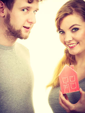 Housing property ownership marriage family future mortgage concept. Young enamoured pair showing house symbol. Man with lady presenting home model.