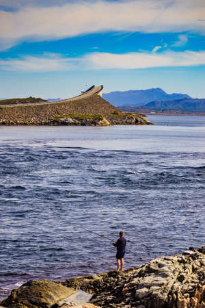 Angler with fishing rod on Atlantic road in Norway Europe. Norwegian national scenic route. Tourist attraction.