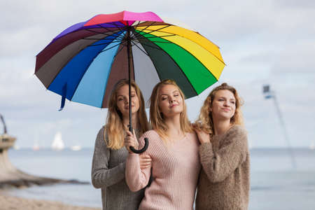 Three pretty young women friends under colorful umbrella parasol. Fashionable females wearing sweaters spending time outdoor. 스톡 콘텐츠