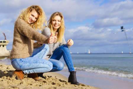 Two fashionable women wearing sweaters during warm autumnal weather spending their free time on sunny beach. Fashion models outdoor 스톡 콘텐츠 - 130066277