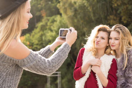 Three females friends having fun during outdoor photo session. Woman taking pictures of two during warm autumn weather. 스톡 콘텐츠 - 130066309