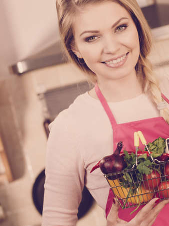 Chef happy woman holding shopping basket with many colorful vegetables. Healthy eating lifestyle, vegetarian food.