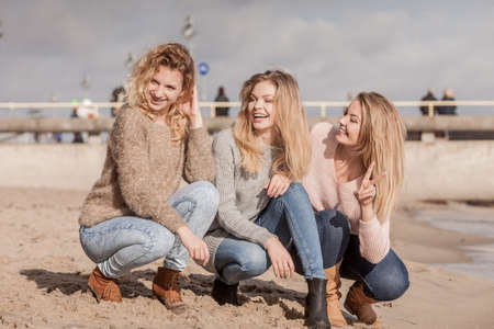 Three fashionable women wearing sweaters during warm autumnal weather spending their free time on sunny beach. Fashion models outdoor 스톡 콘텐츠
