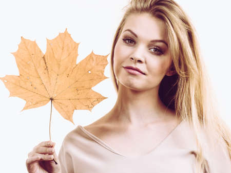 Fashionable autumn long hair blonde girl holding autumnal dry brown maple leaf in hand. Autumn, season and forecasting concept. Banco de Imagens - 130066363