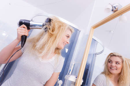 Haircare. Beauty long haired blonde woman drying hair in bathroom. Smiling girl blowing wind on wet head using hairdryer, doing curls with diffuser nozzle. Banco de Imagens - 130066365