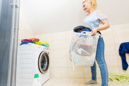 Woman in bathroom carrying big heavy basket of dirty clothes. Laundry concept. Household duties. Standard-Bild - 130066376