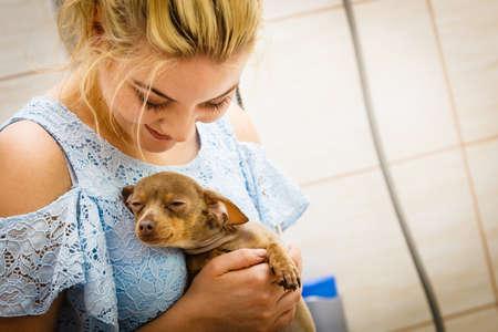 Woman taking care, hugging her little dog pinscher ratter prazsky krysarik. Petting before shower.