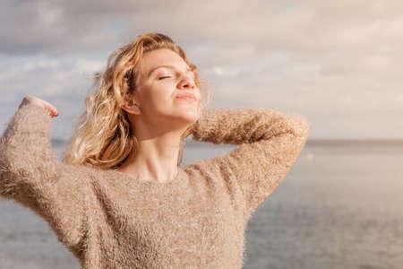 Happy smiling blonde woman portrait. Joyful female being positive walking outdoor wearing sweater having wind tousled hair in sunlight,