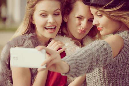 Three females taking selfies, having fun outdoor using smart phone to take photo.