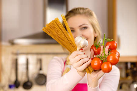 Woman holding long pasta macaron, fresh organic delicious tomatoes and garlic about to cook spaghetti.