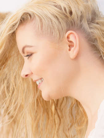 Close up portrait of funny playful female having beautiful blonde dyed fluffy hair. Haircare concept. Banco de Imagens - 130066443