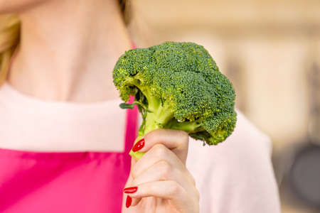 Woman in kitchen holding green fresh broccoli. Housewife cooking. Healthy eating, vegetarian food, dieting and people concept.