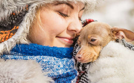 Young woman wrapped her best friend little dog in warm blanket scarf to warm him in cold snowy winter day. Animal protection save. Adoption concept