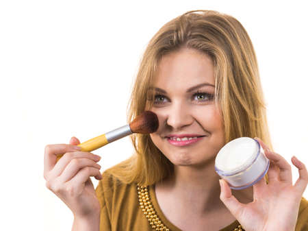 Fashionable cheerful young female holding professional powder brush, adding last touch to her make up 写真素材