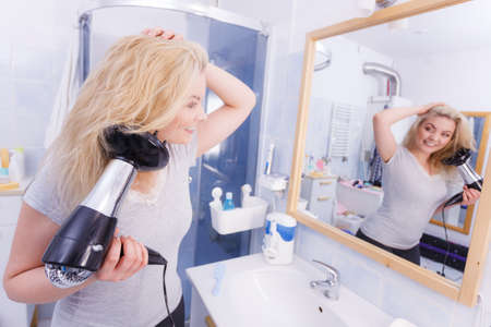 Haircare. Beauty long haired blonde woman drying hair in bathroom. Smiling girl blowing wind on wet head using hairdryer, doing curls with diffuser nozzle. Banco de Imagens